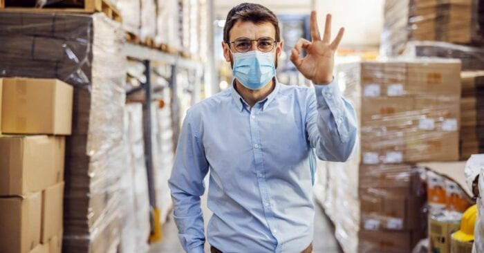man gives ok sign in warehouse