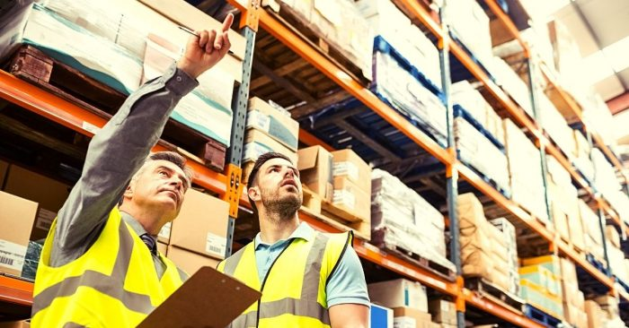 man pointing out box in warehouse